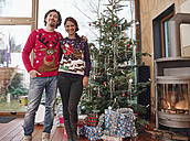 Couple standing in front of Christmas tree wearing Christmas jumpers - RHF001318