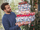 Man carrying stack of Christmas parcels - RHF001324