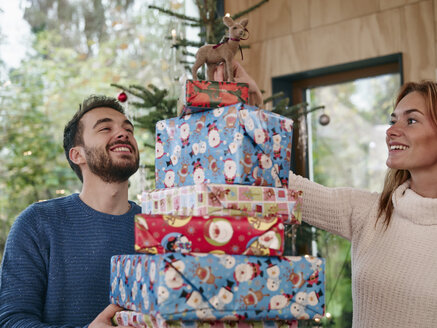 man carrying stack of Christmas presents, woman putting reindeer on top - RHF001327