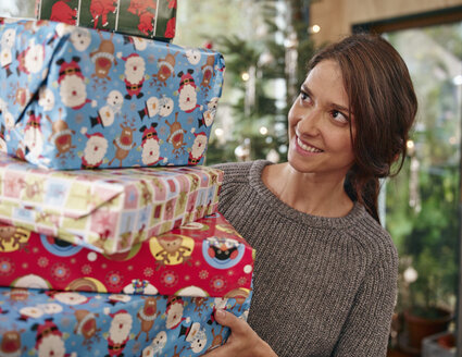 Woman carrying stack of Christmas parcels - RHF001330