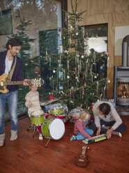 Family playing music together under Christmas tree - RHF001339