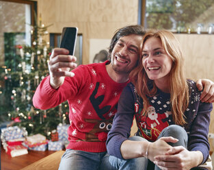 Happy couple taking selfie in front of Christmas tree - RHF001345