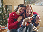 Happy couple unwrapping children's shoes in front of Christmas tree - RHF001348