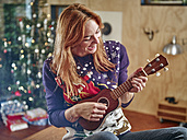 Blond woman playing ukulele in front of Christmas tree - RHF001351