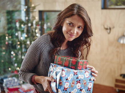 Woman carrying stack of Christmas parcels - RHF001354