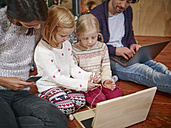 Father using laptop, mother playing with daughters on toy computer on Christmas Eve - RHF001366