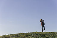 Young couple kissing on a hill in front of blue sky - ABZF000253