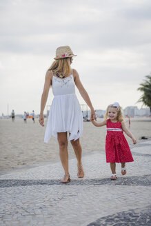 Brasil, Rio de Janeiro, mother and daughter walking on Copacabana beach - MAUF000256