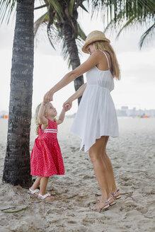 Brasil, Rio de Janeiro, mother and daughter playing on Copacabana beach - MAUF000259