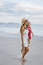 Brasil, Rio de Janeiro, mother carrying daughter on Copacabana beach - MAUF000268