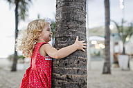 Happy girl hiding behind palm tree trunk - MAUF000277