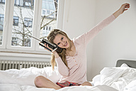 Portrait of smiling young woman sitting on her bed listening music from radio - FMKF002454