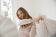 Laughing young woman having pillow fight - FMKF002463