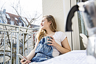 Portrait of young woman sitting on balcony with smartphone and cup of coffee - FMKF002466