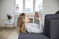 Young woman lying on couch using digital tablet - FMKF002469
