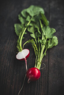 Whole and sliced red radish on dark wood - DEGF000671