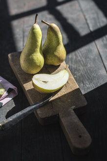 Whole and sliced pears on wooden board - DEGF000677