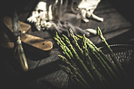 Green asparagus in a wire basket on dark wood - DEGF000686