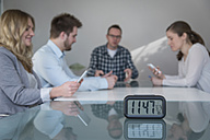 Four colleagues having a meeting with clock in foreground - PAF001580