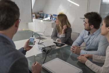 Four colleagues attending a presentation with smartphone and projector in conference room - PAF001589