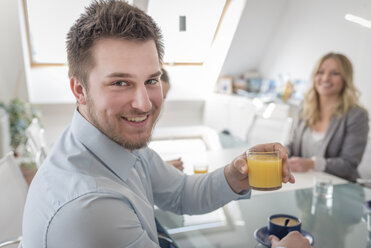 Smiling man holding glass of orange juice in office - PAF001595