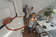 Happy woman playing basketball in conference room - PAF001598