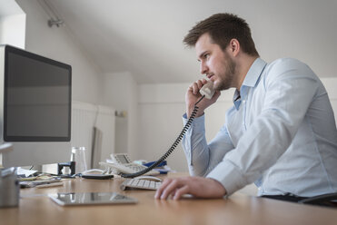 Young man at desk in office on the phone - PAF001610