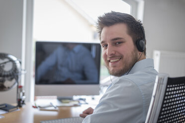 Portrait of smiling young man at desk in office wearing headphones - PAF001613