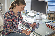 Young woman at desk in office looking at digital tablet - PAF001616