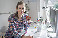 Portrait of smiling young woman at desk in office holding an apple - PAF001619