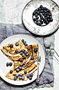 Crepes with blueberries sprinkled with icing sugar on plate - SBDF002696