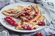 Crepes with red currents sprinkled with icing sugar on plate, close-up - SBDF002699