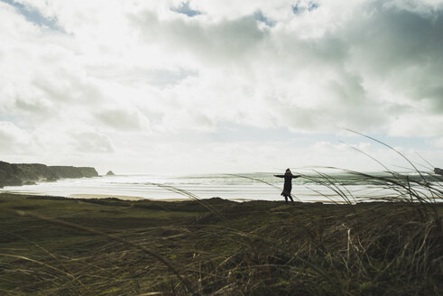 France, Bretagne, Finistere, Crozon peninsula, woman standing at the coast with outstretched arms - UUF006697