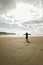 France, Bretagne, Finistere, Crozon peninsula, woman standing on the beach with outstretched arms - UUF006700