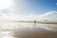 France, Bretagne, Finistere, Crozon peninsula, woman walking on the beach - UUF006703