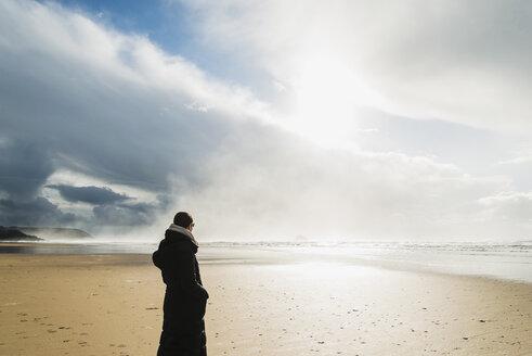 France, Bretagne, Finistere, Crozon peninsula, woman standing on the beach - UUF006712