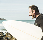France, Bretagne, Finistere, Crozon peninsula, happy man on beach with surfboard - UUF006730