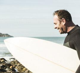 France, Bretagne, Finistere, Crozon peninsula, happy man on beach with surfboard - UUF006730