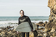 France, Bretagne, Finistere, Crozon peninsula, confident man on rocky beach with surfboard - UUF006733