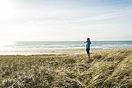 France, Bretagne, Finistere, Crozon peninsula, woman standing at the coast - UUF006736