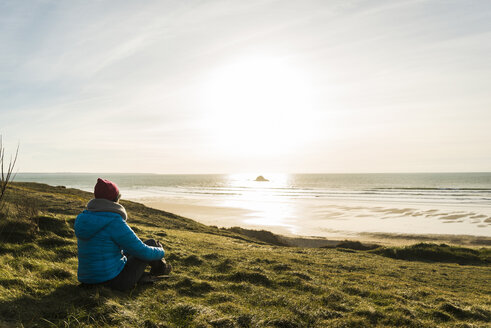 France, Bretagne, Finistere, Crozon peninsula, woman sitting at the coast at sunset - UUF006745