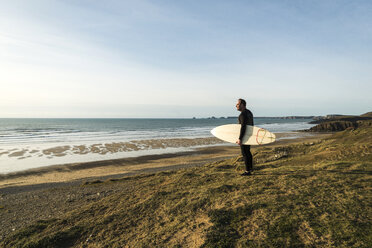 France, Bretagne, Finistere, Crozon peninsula, man standing at the coast with surfboard - UUF006748