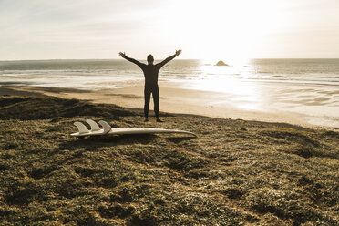 France, Bretagne, Finistere, Crozon peninsula, man at the coast with outstretched arms and surfboard - UUF006751
