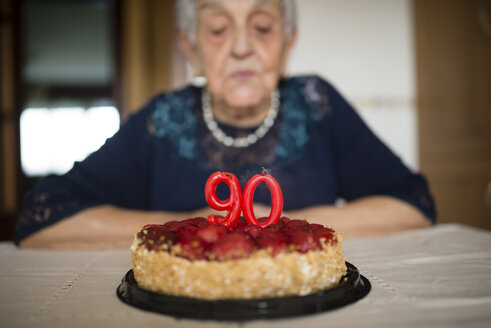 Portrait of senior woman blowing out the candles on her birthday cake - RAEF000930