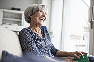 Portrait of happy senior woman sitting on couch at home - RBF004108