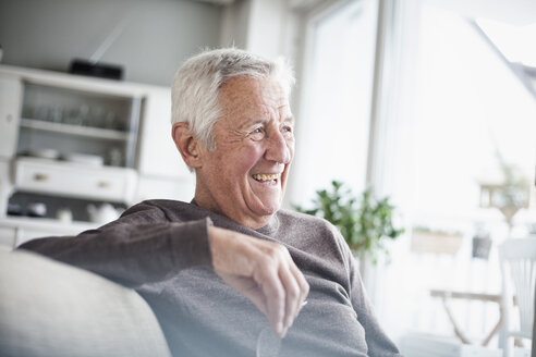 Portrait of laughing senior man sitting on couch at home - RBF004114