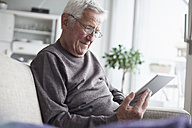 Portrait of senior man sitting on couch at home using digital tablet - RBF004117