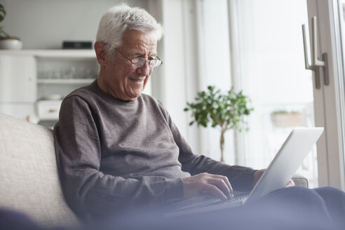 Portrait of senior man sitting on couch at home using laptop - RBF004120