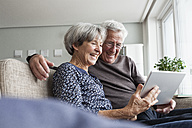 Happy senior couple sitting on the couch in the living room using digital tablet - RBF004123