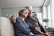 Happy senior couple sitting together on the couch at living room - RBF004126